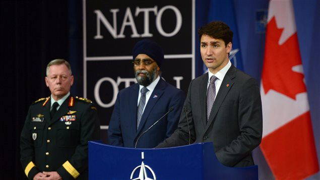Prime Minister Justin Trudeau, right to left, is flanked by Canada's minister of defence and the chief of defence staff at a news conference at NATO headquarters in Brussels, Belgium.