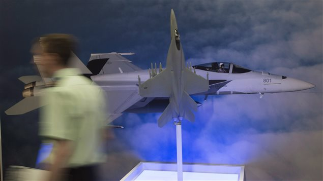 A member of the military walks past the Boeing F/A-18E Super Hornet display at the Canadian Association of Defence and Security conference in Ottawa, Wednesday May 31, 2017. Defence Minister Harjit Sajjan used a major speech Wednesday to the defence industry to blast American firm Boeing for picking a trade spat with Bombardier.