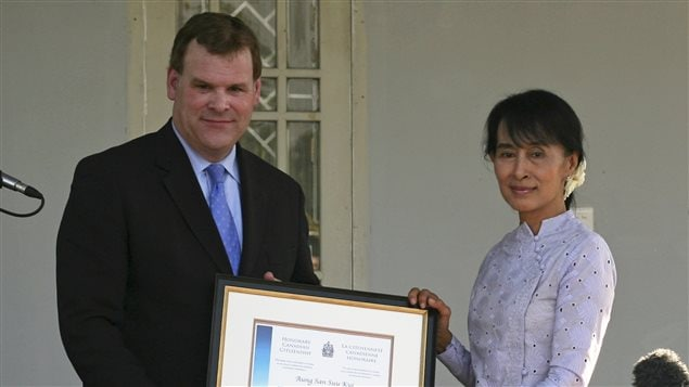Myanmar's pro-democracy leader Aung San Suu Kyi (R) accepts the award of Honorary Canadian citizenship from Canada's Foreign Minister John Baird, after their meeting at Suu Kyi's home in Yangon March 8, 2012.
