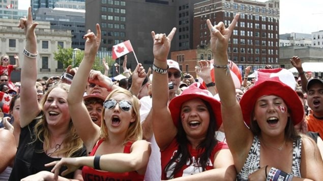 Spectators cheer during Canada Day celebrations on Parliament Hill in Ottawa on July 1, 2012