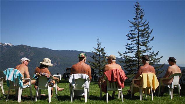 Des gens nus de dos assis sur des chaises face à une montagne.