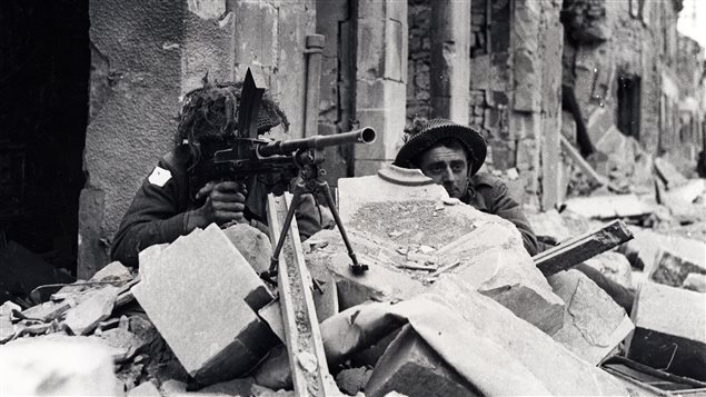 No sooner had the Canadians moved inland after the landings than they were involved in a bitter battle against determined German defenders in Caen. Here two Canadians wtih an Inglis Mk!Bren gun watch for a sniper.
