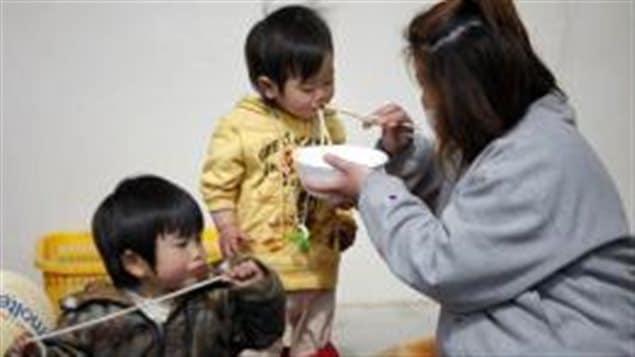 Une femme et ses enfants dans un refuge au Japon.