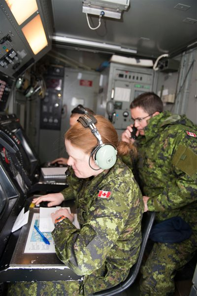 Captain Meghan McCready (left), Aerospace Controller with 12 Radar Squadron, watches the control radar screen while Master Corporal Patrick Flynn (right), Air Control Operator with 12 Radar Squadron, relays the information during Exercise AMALGAM DART 15-2 in Resolute Bay, Nunavut on May 31, 2015.