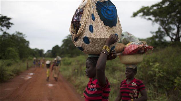 Des femmes transportant des objects sur leur tête sur une route de terre battue.