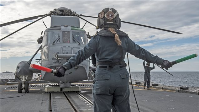 Her Majesty's Canadian Ship Fredericton's Air Detachment deck director signals the deck crew during the start-up of the embarked CH-124 Sea King helicopter on Operation REASSURANCE on March 3, 2015.