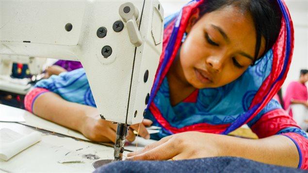 Une fille travaille dans une usine de fabrication des vêtements