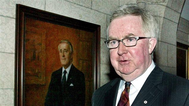 Former Progressive Conservative leader Joe Clark walks past a portrait of former Canadian Prime Minister Brian Mulroney, on Parliament Hill in Ottawa, April 26, 2004.