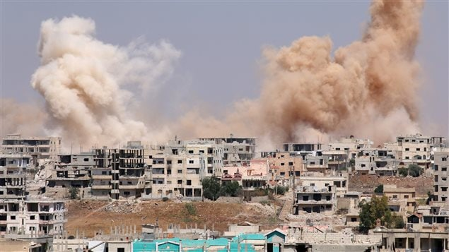 الدخان يتصاعد من أحياء تحت سيطرة قوات معارضة لنظام الرئيس بشار الأسد في مدينة درعا في جنوب سوريا بعد تعرضها لغارات جوية اليوم.