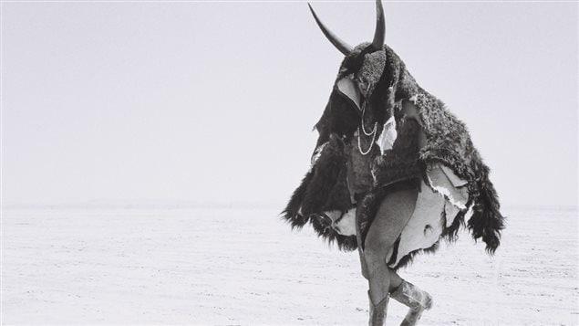Un individu, revêtu d'une peau d'animal, avec cornes, marche dans le désert