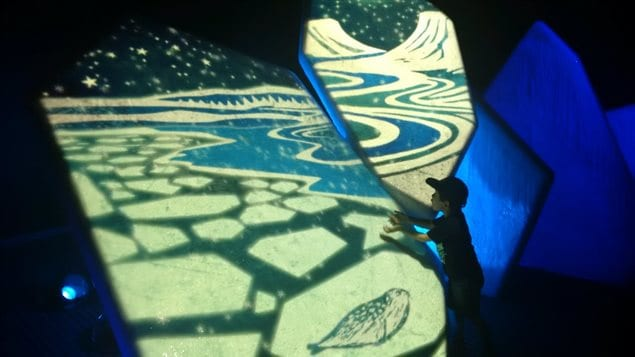 A child reaches out in response to an animation projected onto real ice.