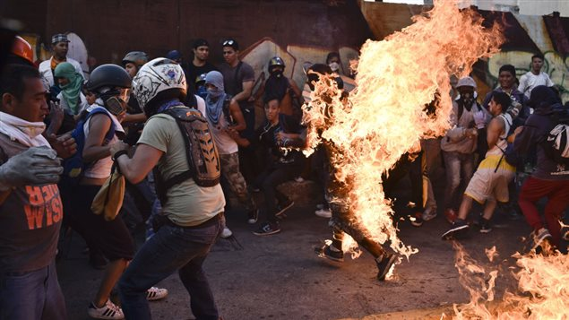 Opposition demonstrators set a man on fire during a protest against the government of President Nicolas Maduro in Caracas on May 20, 2017. According to the Venezuelan Interior and Justice Ministry the victim, Orlando Figuera, 21, was was set on fire after being accused of being a government supporter or a thief. He died of his wounds in hospital on June 5. Figuera had suffered first and second degree burns to 80% of his body and several stab wounds.