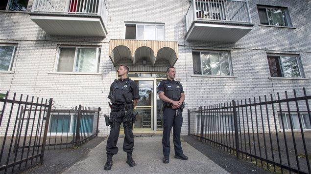 Des policiers montent la garde pendant la perquisition. (Paul Chiasson/Canadian Press)