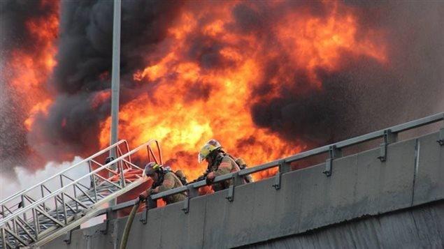 Des pompiers combattent l'incendie sur l'autoroute métropolitainePhoto Credit: Facebook/Brigitte Hébert-Carle