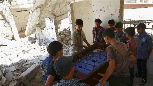 صبية يلعبون كرة قدم الطاولة اليوم في إطار الاحتفالات بعيد الفطر في مبنى مُدمر في مدينة دوما، القريبة من دمشق، التي تسيطر عليها قوات معارضة لنظام الرئيس بشار الأسد والمحاصَرة من قوات النظام.