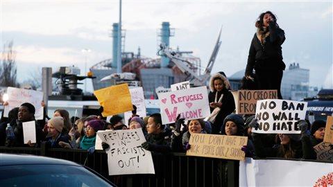 Des manifestants rassemblés le 29 janvier dernier devant l'aéroport international John F. Kennedy, de New York, afin de protester contre les décrets anti-immigration du président des États-Unis, Donald Trump. Photo : La Presse canadienne/Associated Press/Seth Wenig