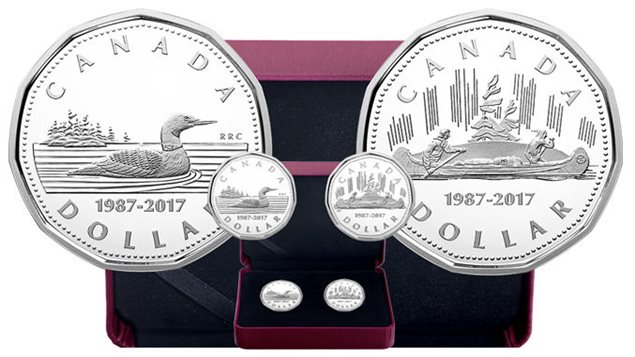 The Mint celebrates the anniversary of the loonie with a special two-coin set of 99.9 % silver coins. These show the typical loon image and the original image of the 1935 silver dollar of the voyageur canoe. The minting is limited to 10,000 sets.