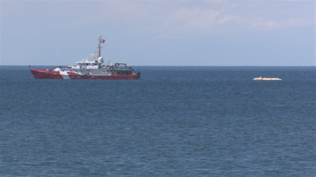 A coast guard ship tows one of the right whales toward shore on Wednesday.