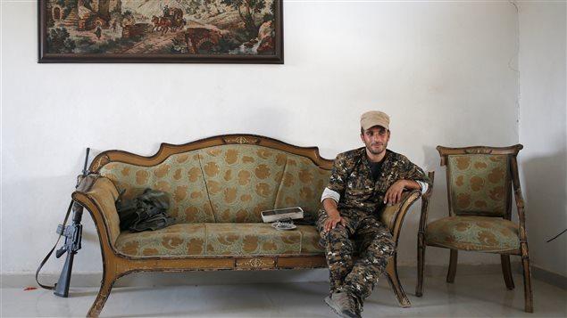 """مقاتل من """"وحدات حماية الشعب"""" الكردية يأخذ قسطاً من الراحة في أحد منازل مدينة الرقة، معقل تنظيم """"الدولة الإسلامية"""" (""""داعش"""") في سوريا، في 3 تموز (يوليو) الجاري."""