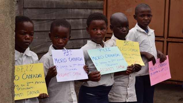 Congolese children display signs saying *Thank you Canada* during the visit of federal International Development Minister Marie-Claude Bibeau in July 2017.