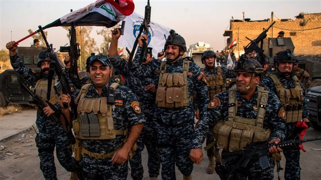 Members of the Iraqi federal police forces celebrate in the Old City of Mosul on July 10, 2017 after the government's announcement of the 'liberation' of the embattled city from Islamic State (IS) group fighters.