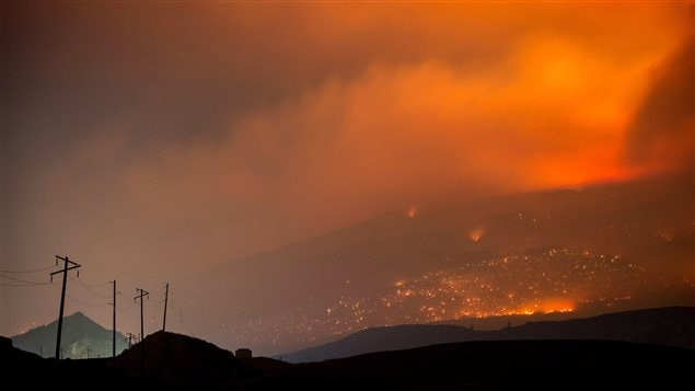 A wildfire burns on a mountain in the distance east of Cache Creek, B.C., in the early morning hours of Monday July 10, 2017.