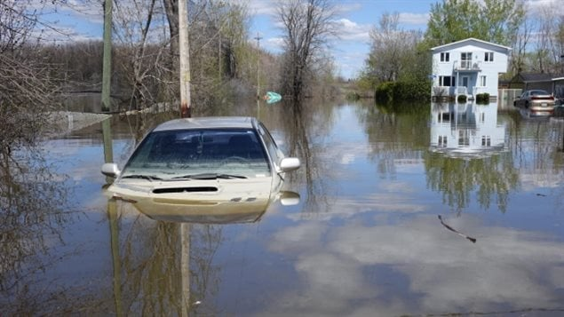 A parked car in flood waters in the Gatineau, Que., area. A new report says preserving wetlands can help reduce the costs of floods. (Ashley Burke/CBC News