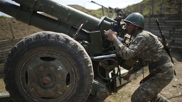 An ethnic Armenian soldier adjusts a cannon's aim at artillery positions near the Nagorno-Karabakh's town of Martuni, April 7, 2016.
