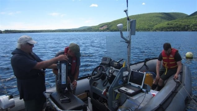 Researchers getting ready to sample onboard a zodiac in Whycocomagh Bay
