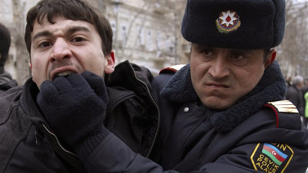 A policeman detains an opposition activist in Baku March 12, 2011.