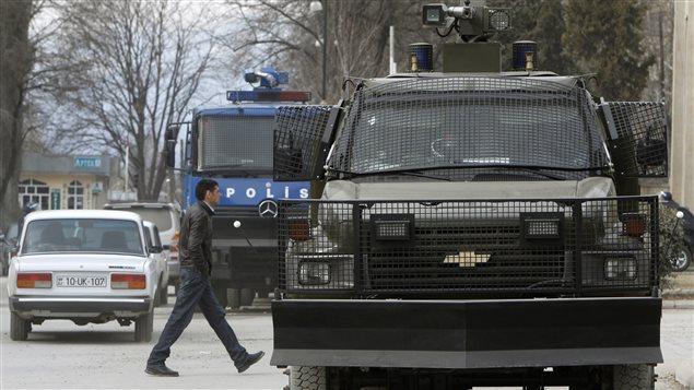 Un résident marche devant des véhicules de police après une manifestation dans la ville d'Ismailli à 200 km au nord-ouest de Bakou, la capitale de l'Azerbaïdjan, en janvier 2013. La police azerbaïdjanaise avait alors utilisé des gaz lacrymogènes et des canons à eau pour disperser des centaines de manifestants.
