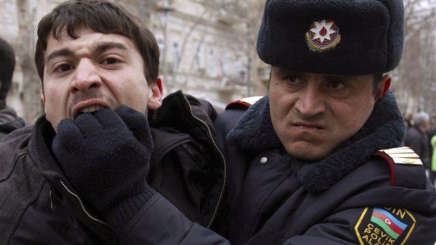 Un policier détient un activiste à Bakou, la capitale de l'Azerbaïdjan, le 12 mars 2011.