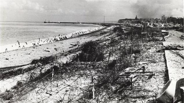 The concrete barriers, wire fencing, and other obstacles on the beach show how well the Germans fortified the Dieppe beach. British intelligence about beach conditions and defences failed miserably leading to the catasophe.