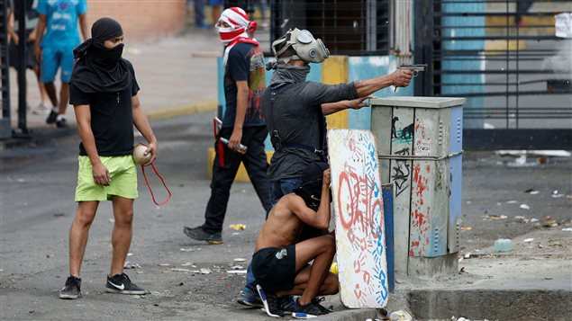 Un miembro de la oposición apunta una pistola contra fuerzas de gobierno durante la jornada de elección de la Asamblea Constituyente en Caracas el 30 de julio de 2017.