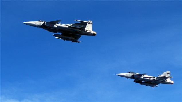 Saab JAS 39C Gripen fighter jets from F17 Wing of the Swedish Air Force demonstrate a mid-air interception over Sweden during a press tour of Swedish air and naval facilities on April 28, 2015.