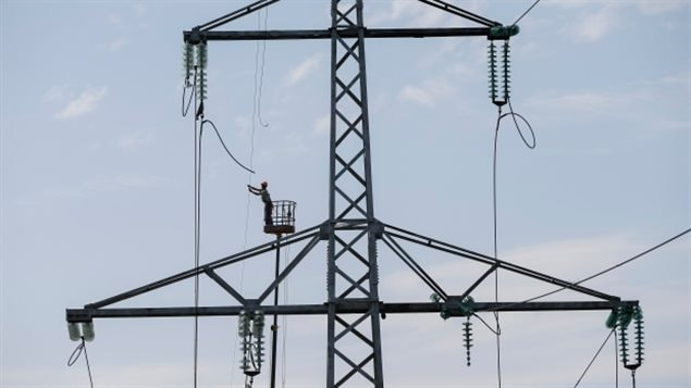 A worker repaired a high voltage line in Ukraine in 2014 after a cyberattack on the power grid.