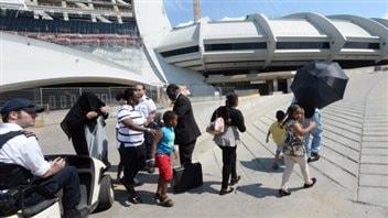 Arrivée de demandeurs d'asile au stade olympique de Montréal. (Ryan Remiorz/Canadian Press)