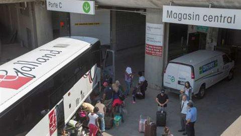Des demandeurs d'asile déchargent leurs affaires en arrivant au stade olympique de Montréal le 2 août 2017. Ryan Remiorz / AP