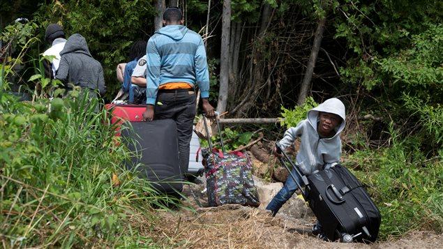 Familia de demandantes de asilo cruzan la frontera canadiense