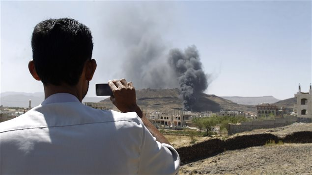 A man films with a mobile phone as smoke rises after explosions were set off at the army's First Armoured Division headquarters in Sanaa October 18, 2012.