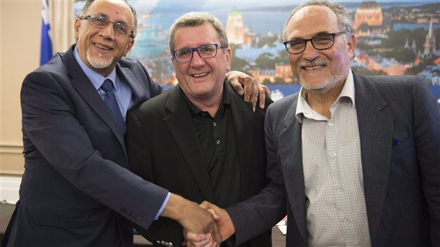 From left to right, Boufeldja Benabdallah, interim coordinator at the Centre Islamique de Quebec, Quebec City mayor Regis Labeaume and Mohamed Labidi shake hands after they announced the establishment of a Muslim cemetery.
