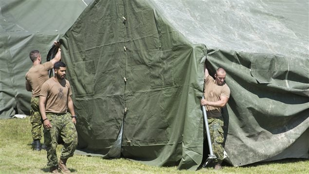 Members of the Canadian armed forces raise a tent to house asylum seekers at the Canada-United States border in Lacolle, Que. Wednesday, August 9, 2017.