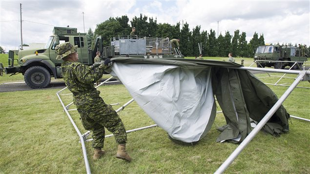 Members of the Canadian armed forces erect tents to house asylum seekers at the Canada-United States border in Lacolle, Que., Wednesday, August 9, 2017.