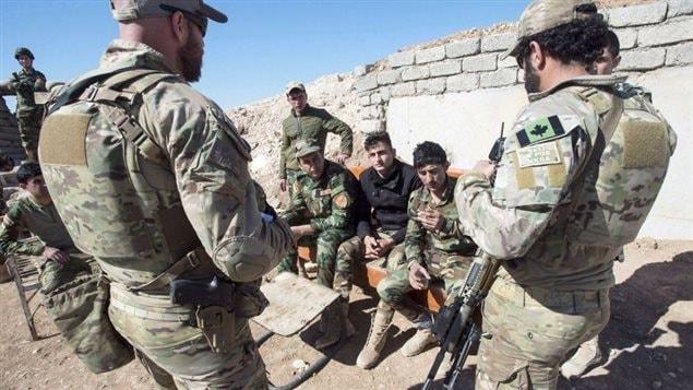 Sur cette photo prise en février 2017, on voit des membres des forces spéciales de l'armée canadienne discuter avec des combattants peshmergas dans le nord de l'Irak.