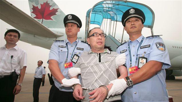 Déporté du Canada, Lai Changxing est arrêté par la police chinoise à son arrivée à Pékin. Photo : Reuters/China Stringer Network