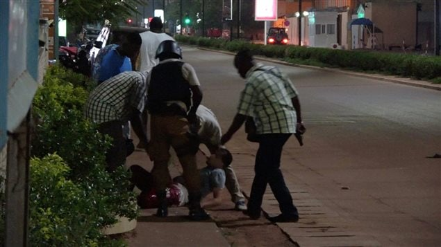 A wounded unidentified person is evacuated following an attack by gunmen on a restaurant in Ouagadougou, Burkina Faso, in this still frame taken from video August 13, 2017.