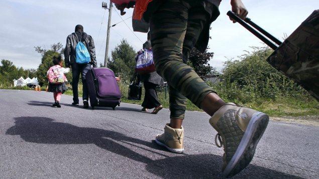 Une famille de demandeurs d'asile arrivant des États-Unis traverse la frontière canadienne cet été.
