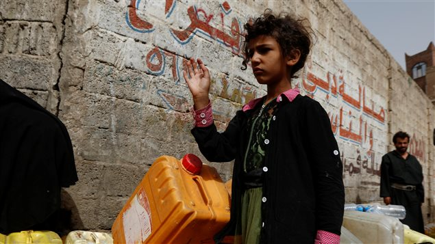A girl stands by jerrycans on a street where a charity tanker truck delivers free drinking water, amid a cholera outbreak, in Sanaa, Yemen, July 10, 2017.
