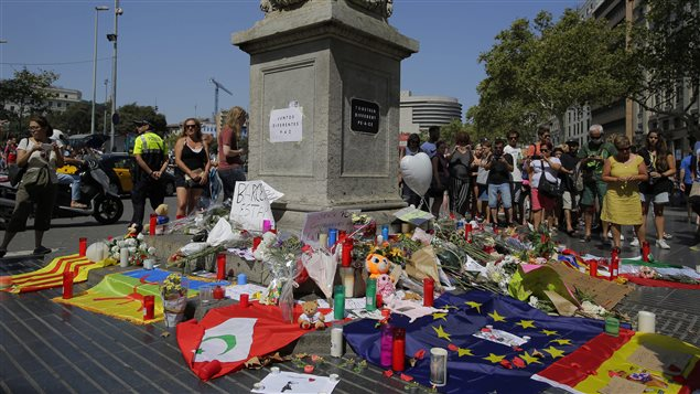 People look at flags, messages and candles placed after van attack that killed at least 13, in central Barcelona, Spain, Friday, Aug. 18, 2017.