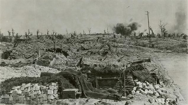 A German shell bursts in a blasted landscape near a Canadian gun pit at Hill 70. The howitzer has a net draped over it, presumably to conceal it from possible enemy spotter planes. Part of the wheel and gun trail can be seen